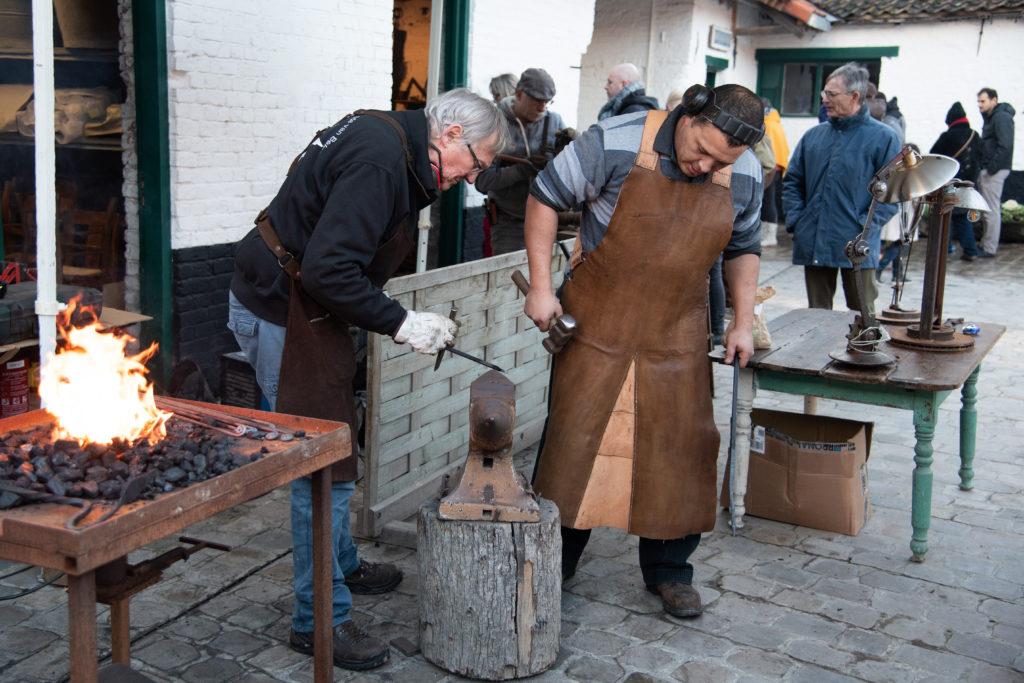 Deux artisans du métal travaillent une pièce